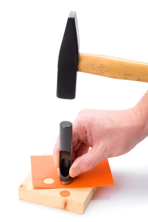 puncher: Human hand making holes using hole puncher and hammer Stock Photo