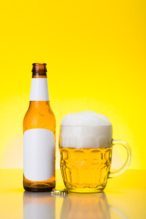 foamy: Mug with foamy beer and empty bottle with blank labels on yellow background Stock Photo