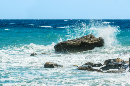 hitting: Moderate sea waves hitting the rocks near the beach Stock Photo
