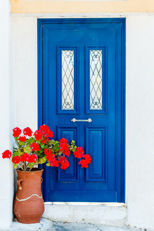 vasi greci: Blue Greek house door with geranium (Pelargonium) flowers Archivio Fotografico