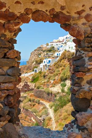 view through door: View on the modern apartments in Oia through ruined house door, Santorini island, Greece