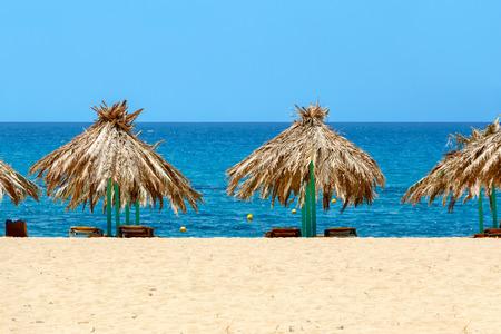 ios: Blue sea, golden sand, sunbeds and umbrellas on the beach. Ios island, Greece Stock Photo