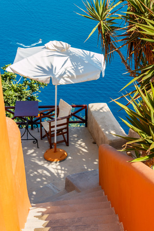 ocean plants: Small terrace of an apartment with umbrella, desk and chair in Oia town, Santorini island, Greece