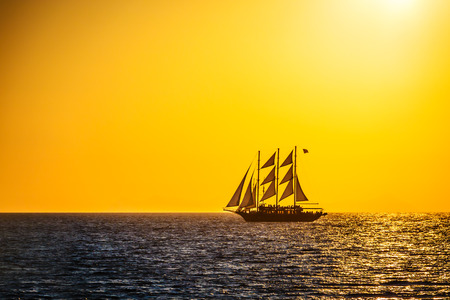 Sailing ship silhouette in red sunset on the sea