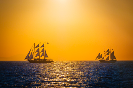 water transportation: Sailing ships on the sea in red sunset Stock Photo