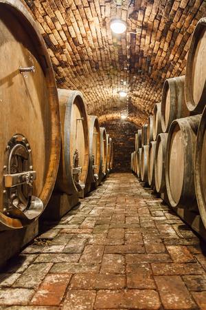 Rijen van eiken vaten in ondergrondse wijnkelder Stockfoto