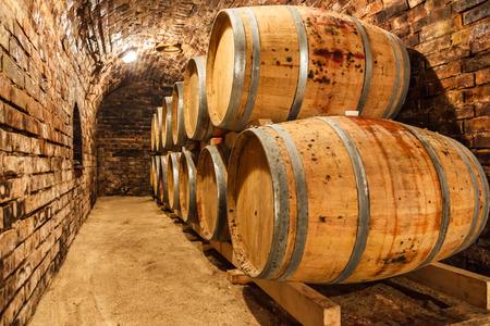 Rows of oak barrels in underground wine cellar Foto de archivo