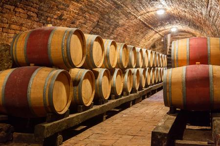 barrels: Rows of oak barrels in underground wine cellar Stock Photo