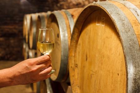 blanc: Une main tenant un verre de vin blanc froid en face de fûts de chêne Banque d'images