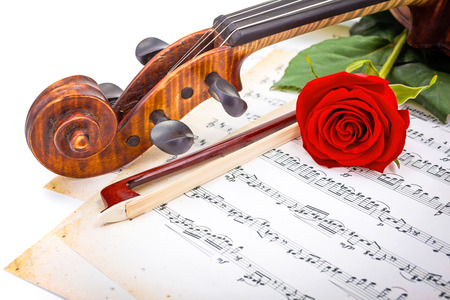 Close view of violin scroll, bow and red rose on musical sheet Stock Photo