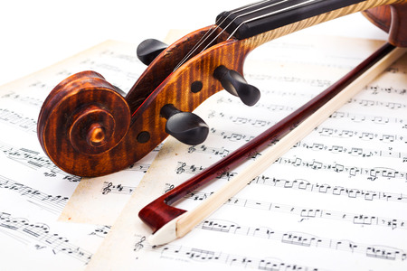 Close view of violin scroll and bow on musical sheet Archivio Fotografico