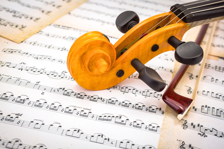 Close view of violin scroll and bow on musical sheet Stock Photo