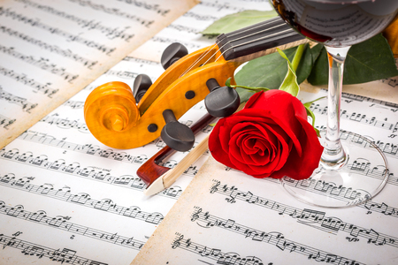 Close view of violin scroll, bow, red rose and wine on musical sheet