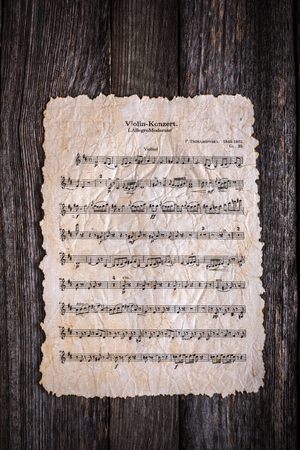Old, torn paper musical score on old wooden background