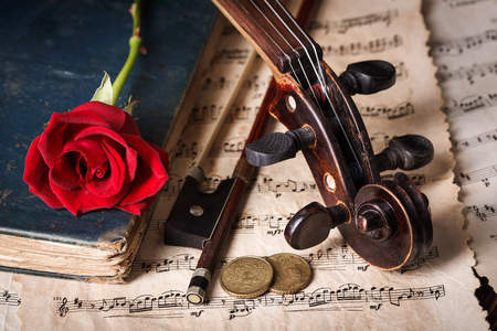 Close view of an old violin scroll, books, bow, money and musical sheets