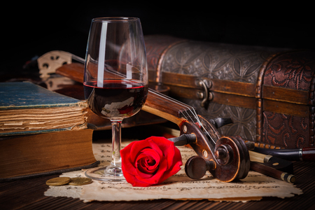 Romantic image detail with violin scroll, wine glass, books and red rose Banque d'images