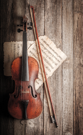Classical used violin, bow and musical score on old wooden background Banque d'images