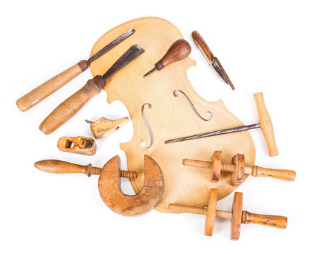 Violin belly and different work tools on white background