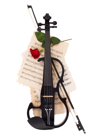 Electric violin, bow, red rose on musical sheets