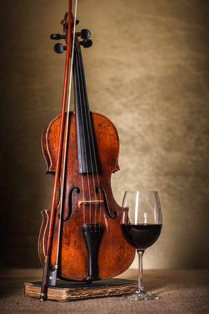 Front view of a classical old violin with red wine glass