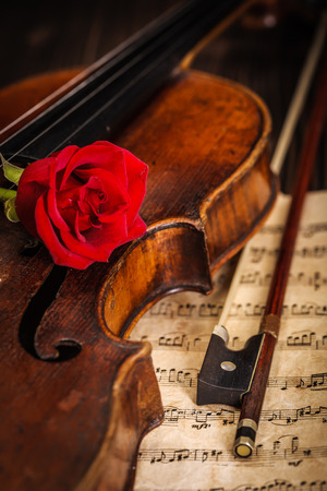 Details: old violin and bow with red rose on wooden background