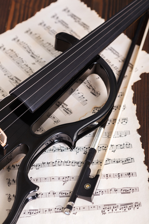 Electric violin detail and bow on musical score background Banque d'images