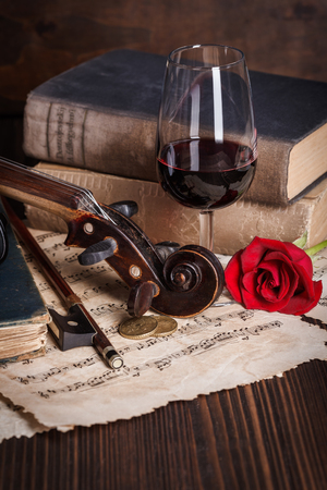 Old books, violin scroll and red rose on wooden background