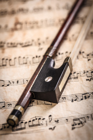 Violin bow on old musical sheets