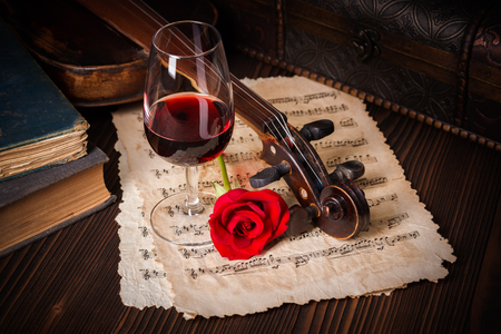 Romantic image detail with violin scroll, wine glass, books and red rose Standard-Bild