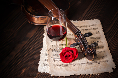 Romantic image detail with violin scroll, wine glass and red rose