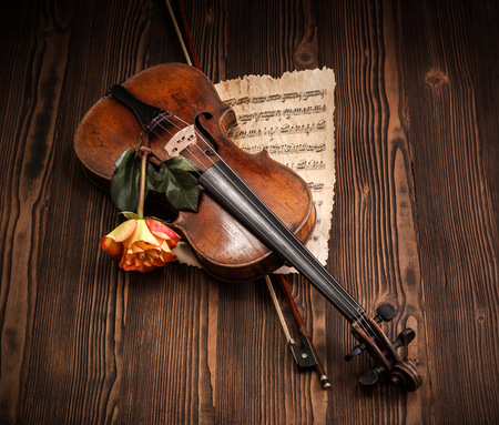 Old violin, bow and musical score with rose on wooden background