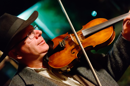 Musician in hat playing on violin in the night Banque d'images