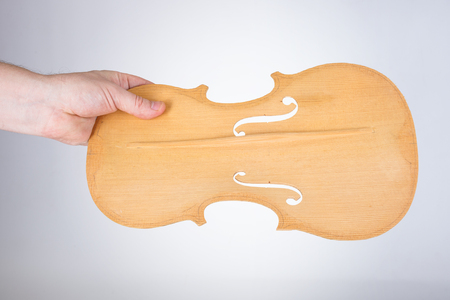 Luthier holding raw violin belly with bass bar
