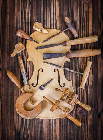 Violin belly and different work tools on wooden table