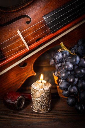 Candle, pipe, violin and red grape on wooden background Banque d'images