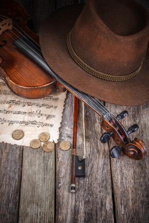 Brown musician hat, violin and coins on wooden table