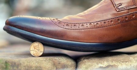 parsimony: Brown leather shoe stepping on a coin standing on edge - 1 cent with the image of Lincoln