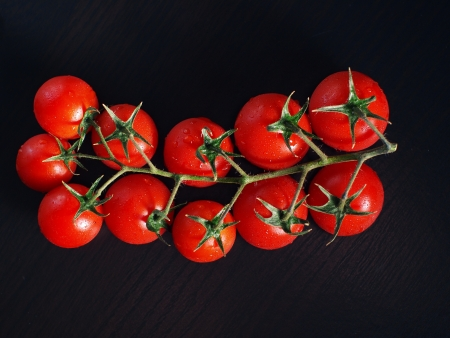 Branch of cherry tomatoes on black wooden board Stock Photo - 17598847