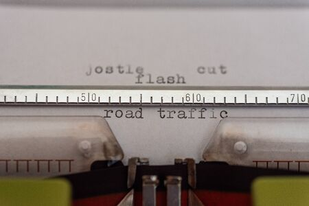 Typewriter with a leaf and the words jostle, cut, flash and road  traffic