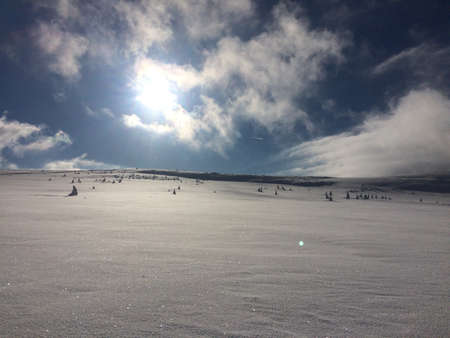 sun on horizon of hill covered in snow in the middle of winter. Giant Mountains, Czech republic