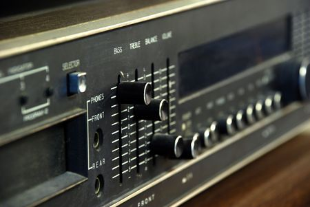 A closeup of a 1970s era black stereo focused mostly on the bass lever, which is raised to the top.