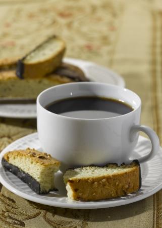 A Broken Biscotti (Italiaanse koekjes) op een schotel met een kopje koffie