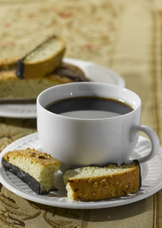 A Broken Biscotti (Italian Biscuit) on a saucer with a cup of coffee photo