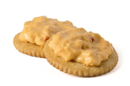 Pimento Schmelzkäse auf Cracker, isoliert auf weiß. Standard-Bild
