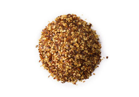 pepper flakes: A pile of crushed red pepper flakes on white with slight shadow.