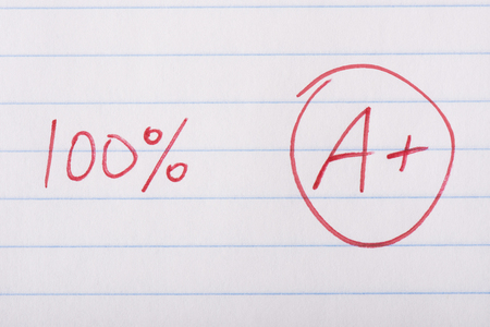 red pen: A plus (A+) grade with 100 percent written in red pen on notebook paper.