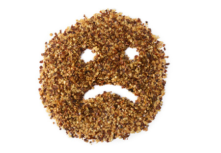 pepper flakes: A pile of crushed red pepper flakes showing a sad face, depicting heartburn or indigestion.