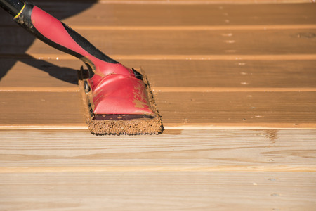 staining: Staining a wooden deck with a staining pad.