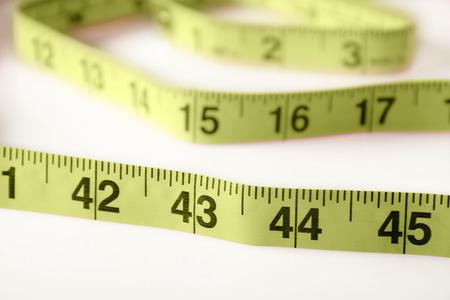 slight: Measuring tape on white with slight shadows. Stock Photo