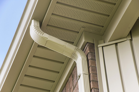 Gutter and downspout near the roof of a house. Stockfoto